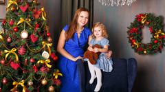 Stock Photo of Mother and daughter near Christmas tree. Home/