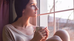 Young sad woman sits on windowsill and drinks coffee Stock Footage