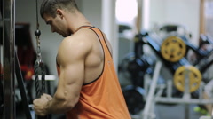Male bodybuilder athlete at the simulator is in a bright shirt, and in the Stock Footage