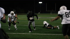 A football player fights his way down the field toward the end zone at night - stock footage