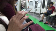 Stock Video Footage of 4K Asian woman using smartphone in subway see the picture phone in Korea-Dan