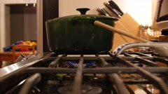 A green pot sits over a gas burner flame Stock Footage