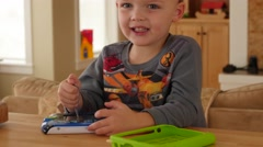 A little boy playing games on a childrens tablet Stock Footage