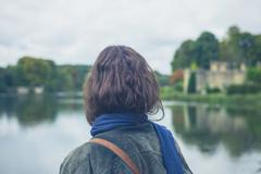 Young woman by lake in formal garden Stock Photos