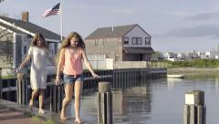 Teens Balance On Sea Wall In Nantucket Island, American Flag Blows In Breeze Stock Footage