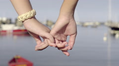 Closeup Of Teen Girls Holding Hands In Front Of Marina With Sailboats - stock footage
