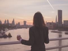 Businesswoman with cup admiring sunrise in London - stock photo