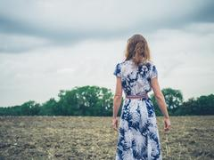 Young woman standing in barren field on cloudy day - stock photo