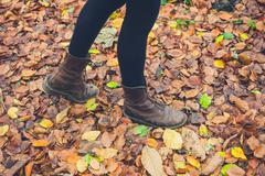 Feet of woman walking in leaves - stock photo