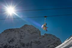 Ski lifts shot against bright sun in mountains Stock Photos