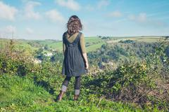 Woman admiring countryside from hill Stock Photos