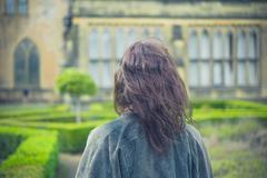 Young woman exploring formal garden - stock photo