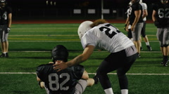A football player helps his opponent up off the ground after being tackled - stock footage