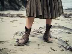 Feet of young woman wearing boots on beach Stock Photos