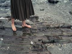 Feet of young woman walking on rocks in water - stock photo