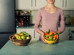 Young woman with apples and oranges in kitchen - stock photo