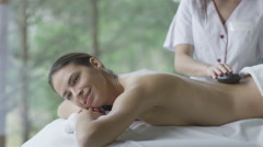 Young brunette woman is getting a relaxing stone massage in wellness center - stock footage