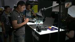 Person checking out camera at Photo Fair 2015 at BITEC in Bangkok, Thailand Stock Footage