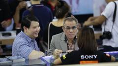 People enquiring at a stall at Photo Fair 2015 at BITEC in Bangkok, Thailand Stock Footage