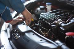Car mechanic working in auto repair service - stock photo