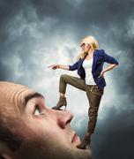 Woman standing on male face Stock Photos