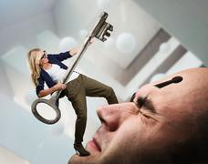Woman with key on the man's face - stock photo