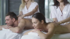 Young couple is getting a relaxing massage from female masseurs Stock Footage
