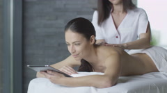 Young brunette woman is using a tablet during a relaxing massage - stock footage