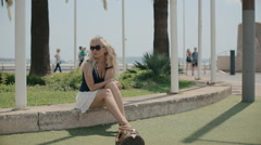 Sexy tourist crouched down on the curb in Cannes Stock Footage