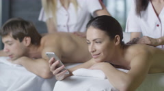 Young woman is using a smartphone during  a relaxing couple massage from masseur Stock Footage