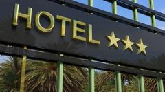 Metallic glass hotel sign board with three golden stars, text and palm trees  - stock illustration