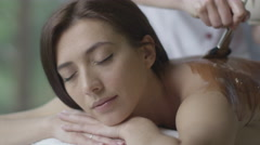 Young beautiful woman is getting a relaxing chocolate massage treatment Stock Footage