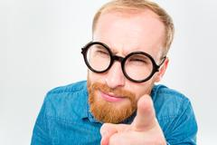 Suspicious bearded man in funny round glasses pointing on you Stock Photos