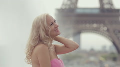 Laughing girl dressed in a pink strapless dress near the Eiffel Tower Stock Footage