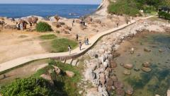 Tourists walk around Yehliu Geopark ways, concrete footpath, natural landscape Stock Footage