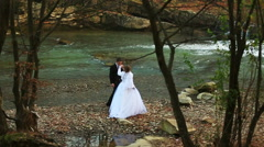 Groom holds his bride's hand in the forest near the river Stock Footage