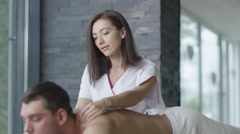 Handsome man is getting a relaxing massage from a woman masseur - stock footage
