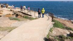 Cheerful Asian girl come towards at footpath, Yehliu Geopark passage Stock Footage