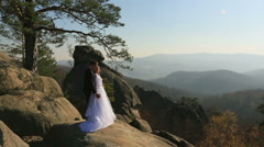 Groom hugs bride on a hillside on the background of  the mountains - stock footage