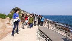 People walk along windy catwalk path along Yehliu Geopark shore Stock Footage