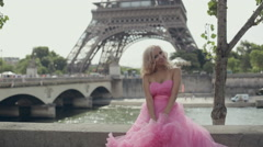 Happy woman dressed in festive pink dress sits next to the River Seine in the - stock footage