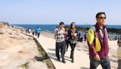 Asian people walk along pathway, sunny Yehliu Geopark cape view Stock Footage