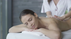 Beautiful woman is getting a relaxing massage from a female masseur - stock footage