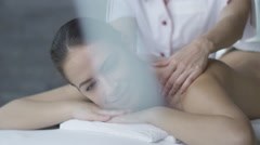 Woman is getting a relaxing massage from a female masseur in wellness center Stock Footage