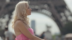 Attractive girl dressed in a pink dress pensively standing near the Eiffel Tower Stock Footage