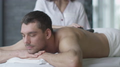 Man is getting a relaxing stone massage from a woman masseur in wellness center - stock footage