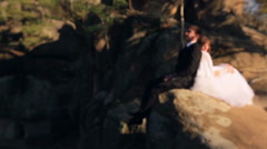 stylish groom and happy young bride sitting on the stone in the forest - stock footage