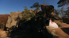 the bride and groom are sitting back to back on the mountain - stock footage