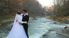 young bride and stilish groom kissing on the background of the river - stock footage