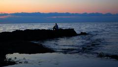 Pensive Guy on Rocks Sihouette Stock Footage